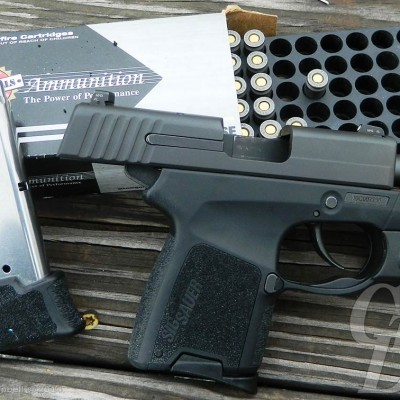 Black SIG P290 with boxes of ammo on a wood plank background