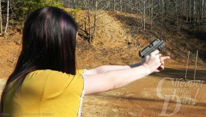 Young, dark haired woman in yellow shirt fires the P290 at a targe.