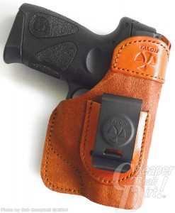 Black handled Smith and Wesson Shield 9mm in a light brown Talon IWB on a white background