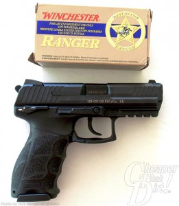 Tan box of Winchester ammunition above a black handgun, barrel pointed to the right, on a white-to-gray background