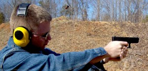Young  man in long sleeved denim shirt with yellow ear protection firing a Glock 19 9mm at a target, with a wooded area behind him