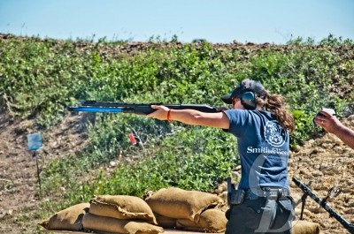 Picture shows competitive shooter, Lena Miculek shooting a 3-gun match with a shotgun.