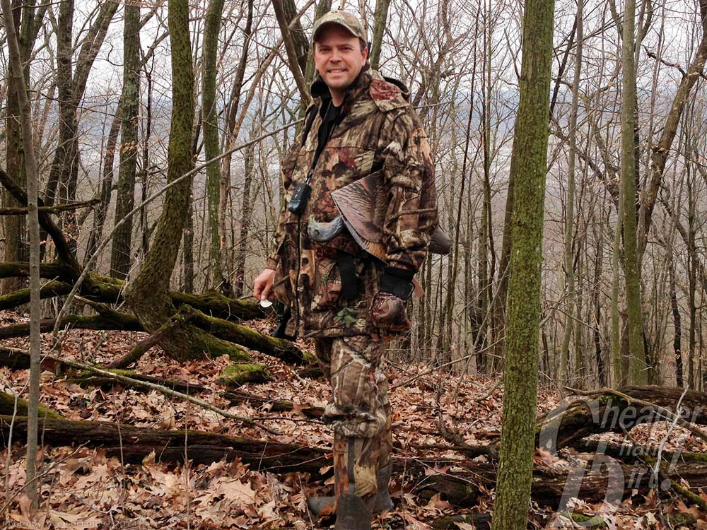 Hunter wearing camo in woods.