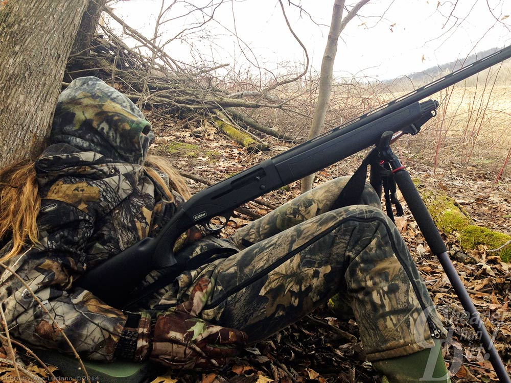 Young hunter with rifle on bipod in woods