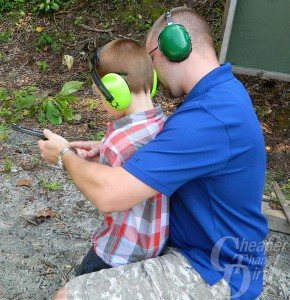 Young father in blue shirt and green ear protection teaches a little boy in a plaid shirt how to shoot the right way, with a wooded area in the background