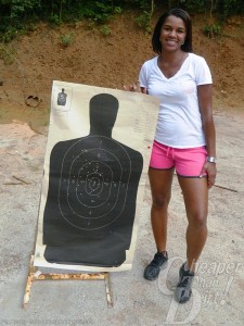 A young woman in a white t-shirt and pink shoots stands by her black target