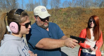 Man in light blue shirt and white ball cap teaches two young ladies how to handle a gun, with a wooded area in the background