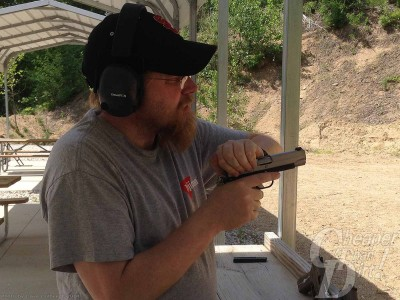 Shooter racking slide of 1911 .45 pistol