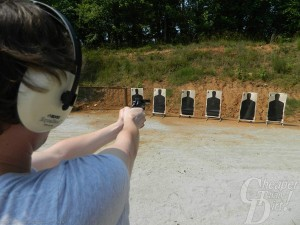 Young man in light blue shirt and ear protection shoots at a series of black paper targets with a wooded area in the background