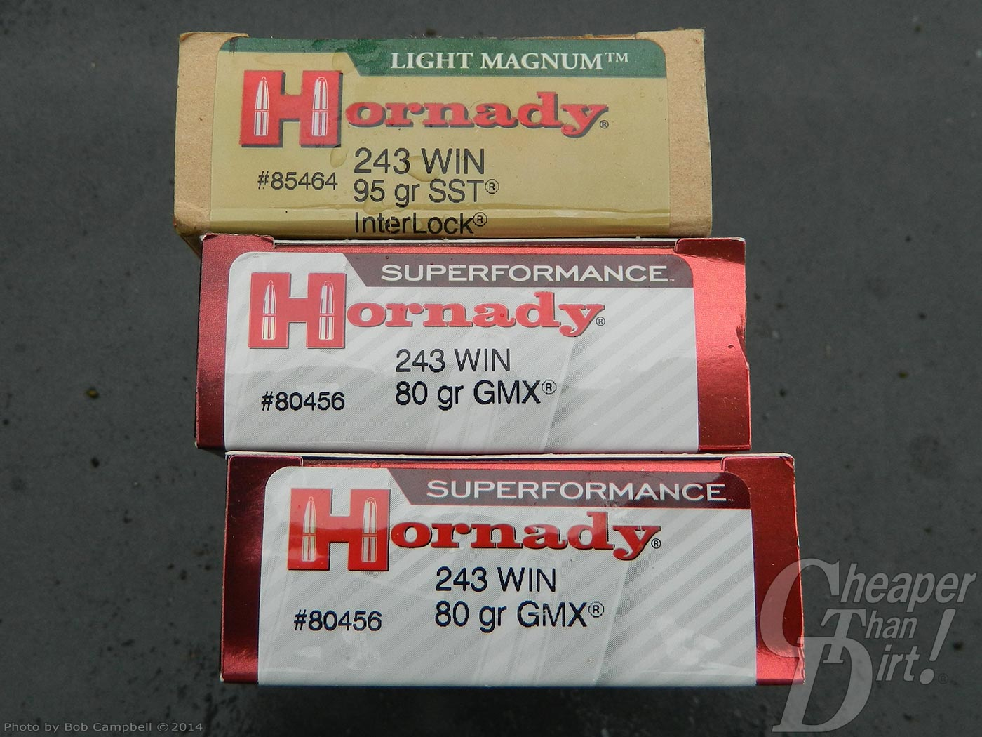 3 boxes of Hornaday ammunition, a light tan box with red lettering, with 2 red boxes of ammo with a white label and red lettering.