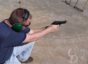 Young man in navy t-shirt and jeans shoots a Beretta 92