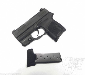 Black compact 9mm with cartridge on white background