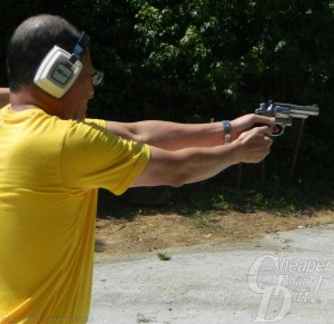 Man in yellow t-shirt points shoots a Smith and Wesson .357 Magum with trees in the background