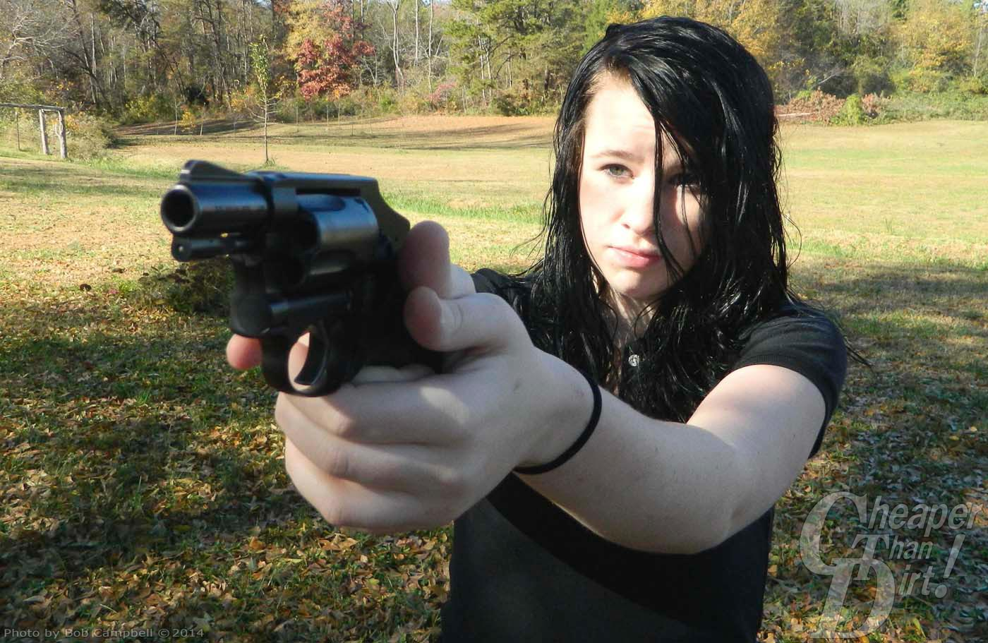 Dark haired woman holding a revolver