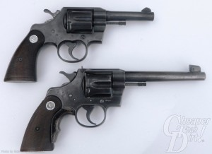 Two stacked revolvers, a four inch .38 on top and a 1930s Colt Tactical on the bottom. Both have black grips and a dark charcoal-colored body, barrels pointed to the right