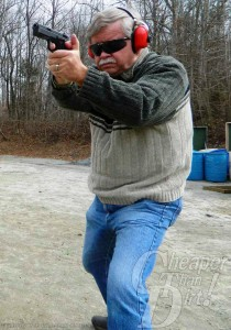 Gray-haired man in gray two-toned sweater and jeans with red ear protection shoots a CZ-75B with a wooded area in the background.