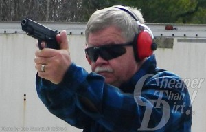 Gray haired man with navy sweater and red ear protection shoots a handfun, facing you