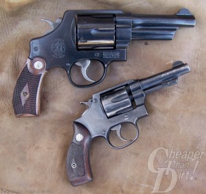 Two brown handled, black barreled revolvers stacked, barrels pointed to the right