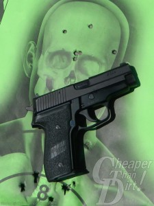 All black SIG P228, barrel pointed up and to the right on a mint green target