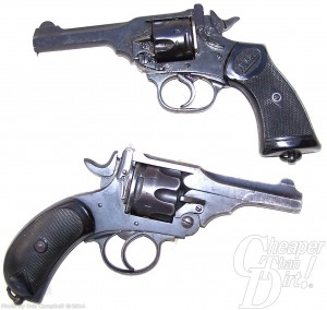 Two stacked guns, a black Webley .455 on top, pointed to the left and a black gripped silver barreled Webley .38 on the bottom, barrel pointed toward the right