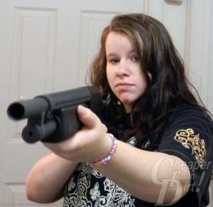 Young dark haired woman shows the Mossberg Cruiser at hand...she is pointing it toward the reader