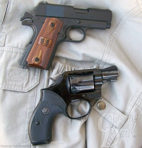 Two handguns, a brown gripped pewter colored on the top, a black snubnose on the bottom, against crinkled white material
