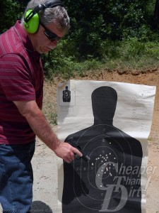 Gray haired man in red shirt with green ear protection points at black target with results of his tests.