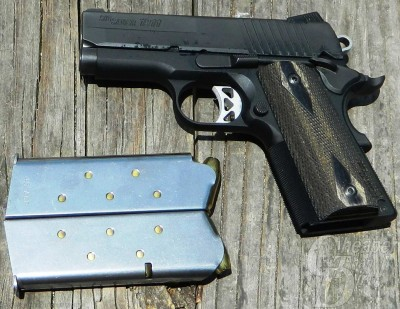 Black SIG Ultra, barrel pointed left and 2 silver magazines on a background of wood planks.