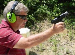 Gray haired man in red shirt with green ear protection practices with his SIG Ultra, with a wooded area in the background