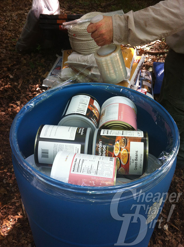 Picture shows a 55-gallopn drum filled with #10 cans of food & The Essential Preppers Guide to Storage