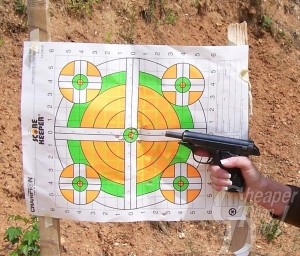 A green white and orange target with a man's hand holding a black handgun pointed at the target