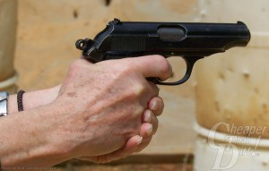 A man's hand holding a black handgun, barrel pointed to the right