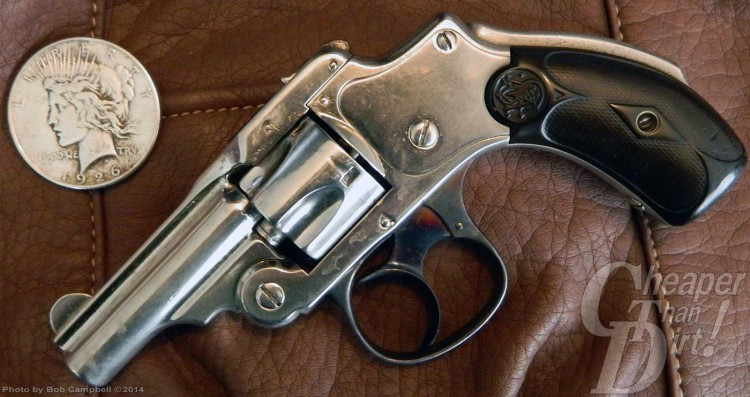 Old silver barreled, black gripped Smith and Wesson bicycle gun on a brown background