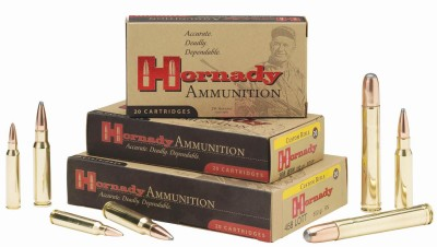 3 Tan boxes of Hornaday 8mm cartridges with red and black lettering stacked on top of each other, with 7 cartridges lying aroud the boxes on a white background