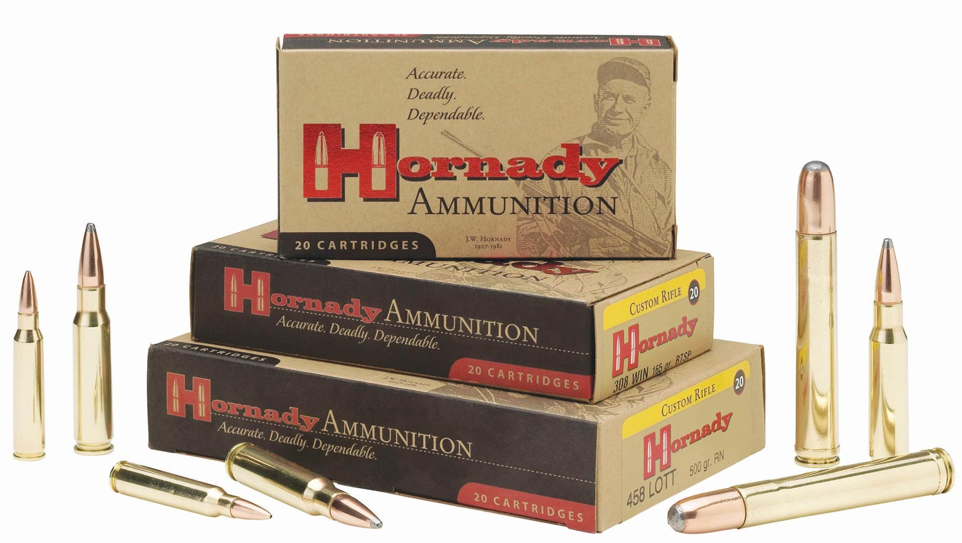 3 Tan Boxes Of Hornaday 8mm Cartridges With Red And Black Lettering Stacked On Top