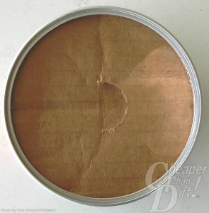 Can of Fiocchi Canned Heat opened to show the light brown substance which is a moisture barrier on a light gray background.