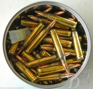 Silver container with gold .223 cartridges on a light gray background