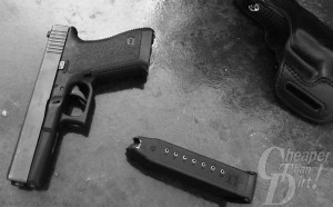 Black GLOCK 21 with a silver slide, barrel pointed down with a black 10-round magazine on a medium gray background