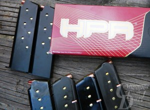 Red and black box of HPR .45 ACP ammunition with 5 magazines, lying on weathered wood