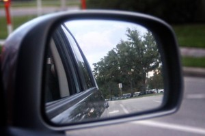 Dark colored outside mirror of a car showing the road behind the driver