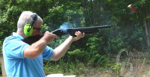 Gray haired man in light blue shirt and ear protection shoots a Mossberg 930 toward a target with a wooded area behind him.
