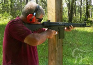 Gray haired man in red shirt and ear protection shows the cocking rod for the black PTR 91 with a wooded area in the background