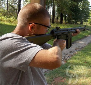 Young man in light shirt and protective eyeware shoots the PTR 91 from a standing position toward a wooded area.