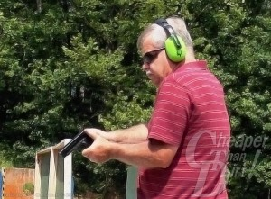 Gray haired man in red shirt, sunglasses and ear protection practices with the P12; trees in the background.