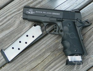 2 silver magazines and a black RIA Tactical compact, barrel pointed to the left,  lying on a weathered board background