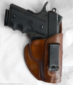 Black RIA Tactical Compact in a brown leather inside-the-waistband holster.