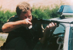 Light haired man in black uniform leans on a silver vehicle, aiming a Ruger Mini 14