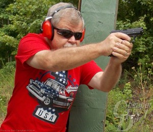 Gray haired man in red shirt and red ear protection drills with 9 mm and .45 loadings, with a wooded area behind him.