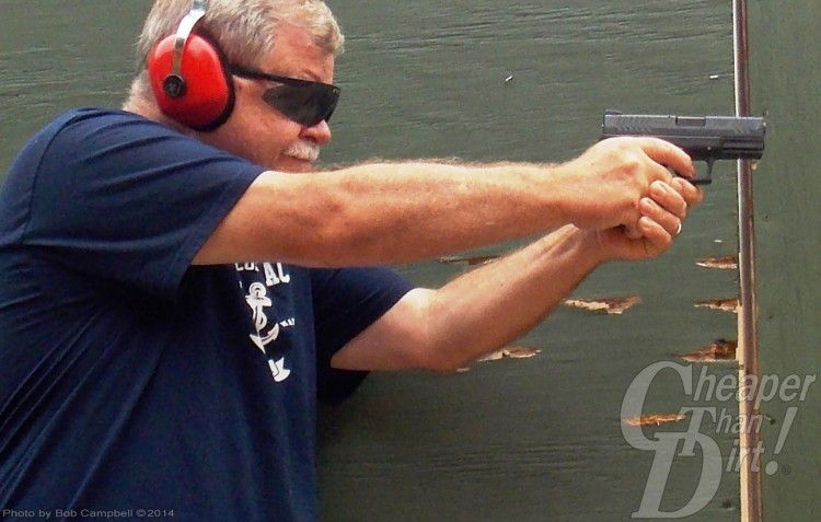 Gray haired man in navy blue t-shirt and red ear protection tests a Springfield XDM at the range.
