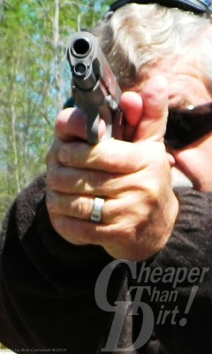 Gray haired man in dark sweater, sunglasses and ear protection tests a Springfield XDM at the range, gun pointed toward the reader